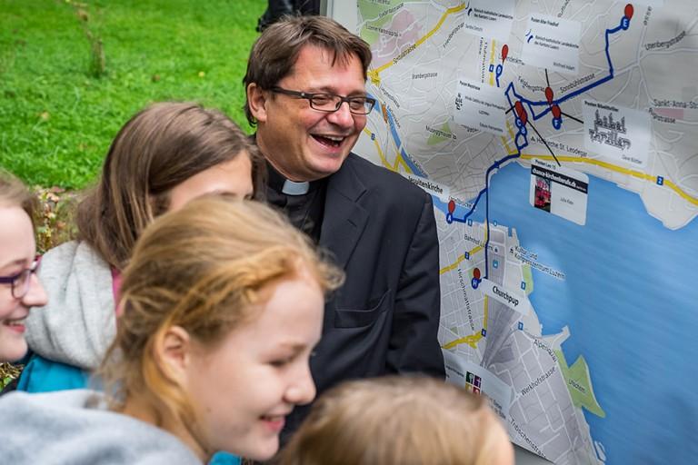 Miteinander Lachen macht fröhlich: Bischof Felix Gmür und Jugendliche vor einer der Routenplakate des Churchtrails. | © 2015 Roberto Conciatori