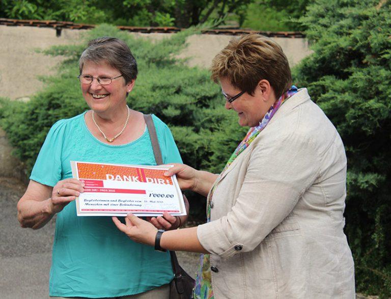 Synodalrätin Annegreth Bienz übergibt Marlis Rinert den Check, der zum «Dank Dir!»-Preis gehört.