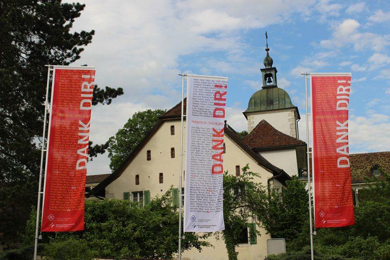 Die «Dank Dir!»-Fahnen flattern im Wind vor dem Centre St. François in Delsberg.