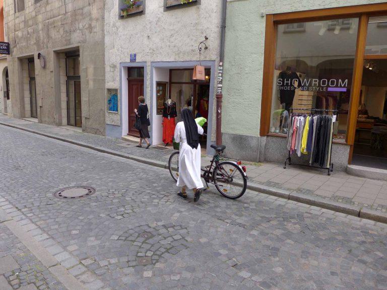 in bescheidenes Verkehrsmittel, ein praktisches aber auch: Nonne mit Fahrrad in der Regensburger Altstadt. | © 2014 Dominik Thali