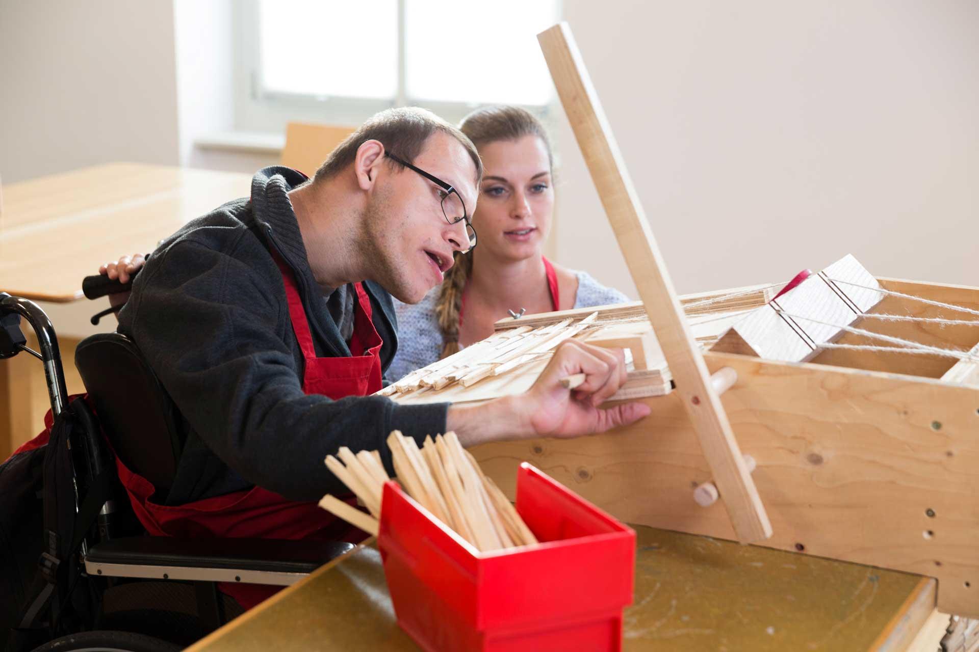 Im Atelier Holz der Stiftung für Schwerbehinderte Luzern SSBL in Rathausen; Arbeitsagogin Franziska Bodul mit Bewohner Muhamet Ibrahimi. | © 2017 Nique Nager