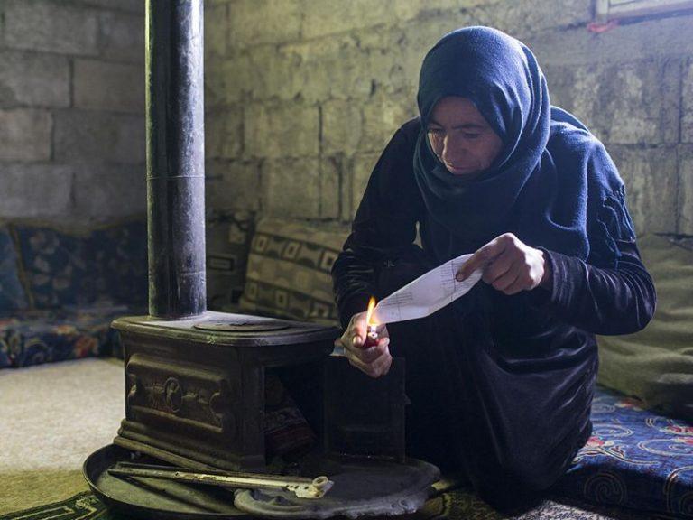 Diese Mutter bemüht sich um etwas Wärme in ihrer kargen Behausung in Jaramana, einem Vorort von Damaskus, wohin sie mit ihrer Familie geflüchtet ist. | © 2017 Caritas Schweiz, Alexandra Wey