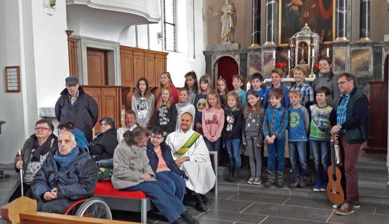In dieser Kirche ists echt gemütlich: Gemeindeleiter Paul Berger und Behindertenseelsorger Bruno Hübscher sitzen mit ihren Gästen auf dem Bett, das im Chor aufgestellt ist. | © 2018 pd