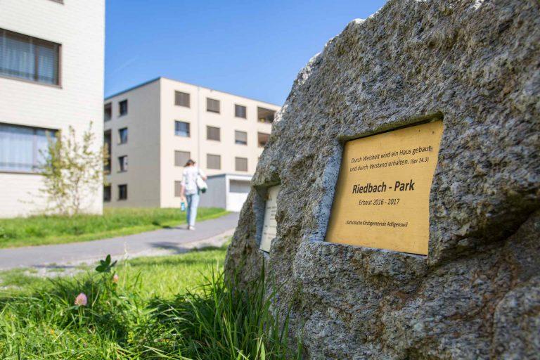 Hier hat die Kirche gebaut: Ein beschrifteter Stein im Riedpark in Adligenswil weist auf die Bauherrschaft hin. | © 2018 Marcel Bucher