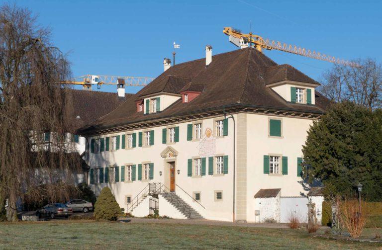 Die beiden Kräne gehören zu einer Baustelle im Hintergrund, sind aber Sinnbild dafür, dass das Kloster Eschenbach (im Bild das Gästehaus mit der Pforte) seine Organisation umgebaut hat. | © 2019 Joe Kaeser