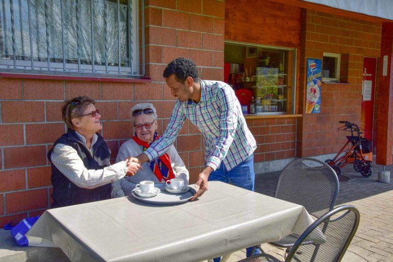 Grüezi! Sala Nasir aus Eritrea, der 2015 nach Aesch kam, bedient im Badikiosk Aesch zwei Gäste. Edith Brunner von der Integrationsgruppe Aesch führt diesen Treffpunkt hauptberuflich. | © 2019 Pirmin Lenherr