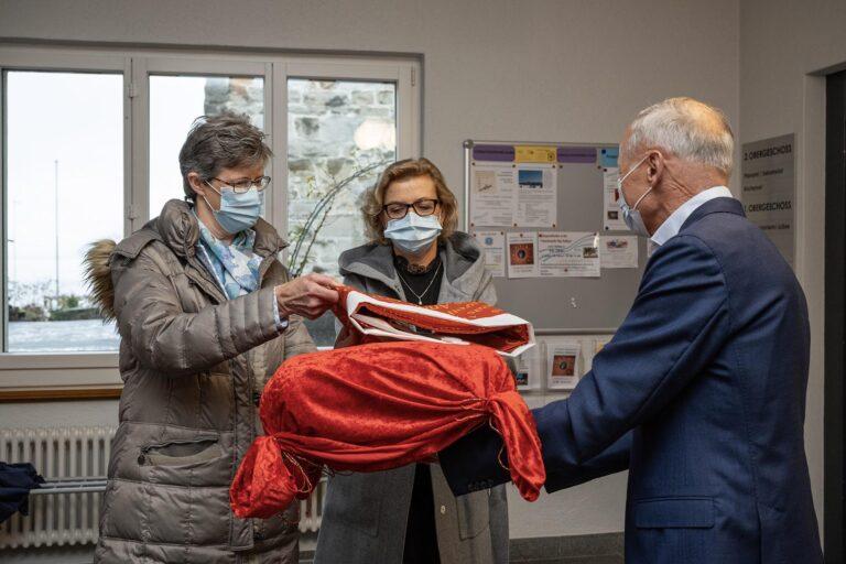 Synodepräsident Martin Barmettler übergibt Lisbeth Hofmann und Carine Sommariva die «Dank dir!»-Fahne, einen der drei Teile des Preises. | © 2020 Dominik Thali