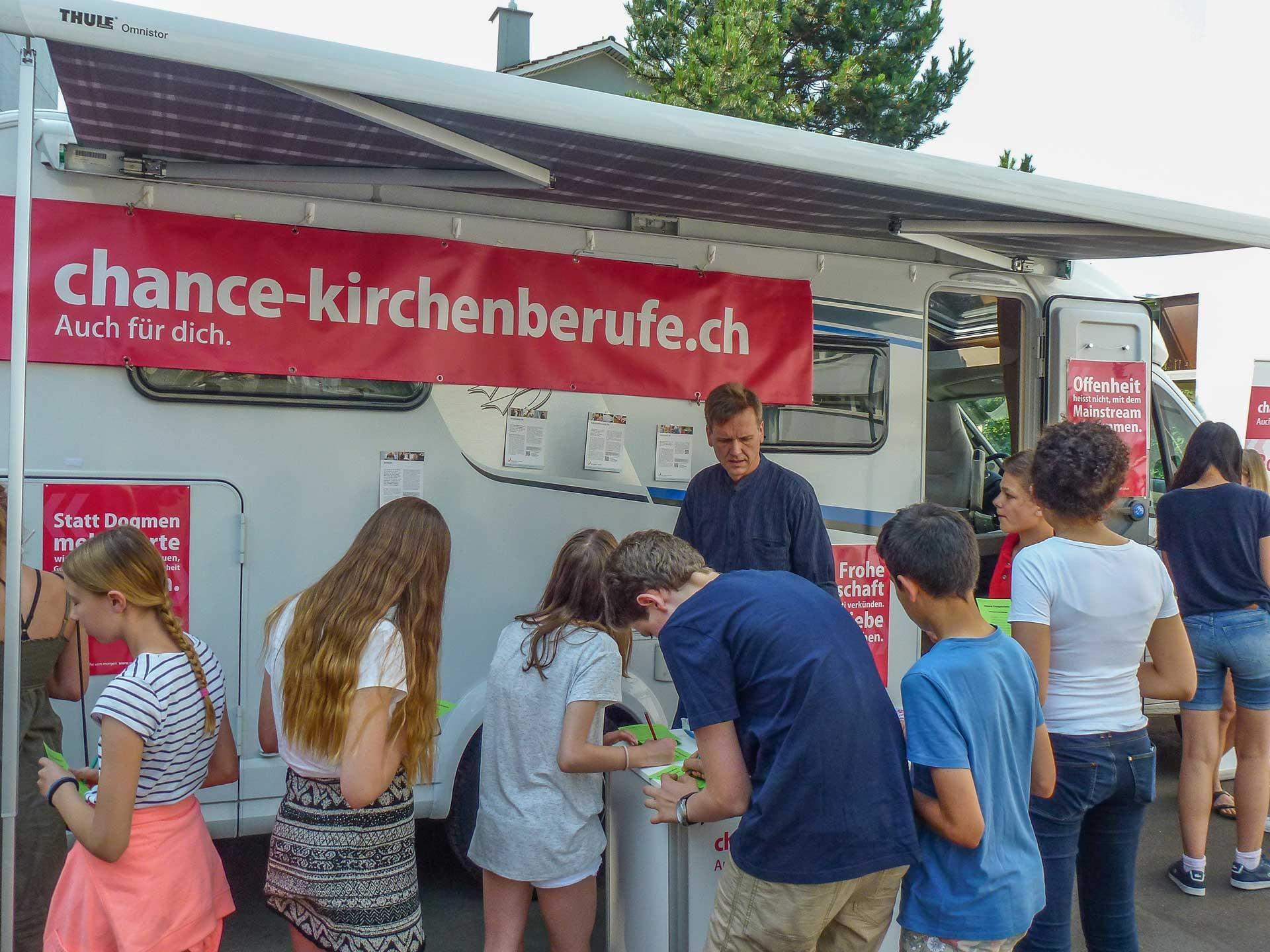 «Ich will nicht schwarzmalen, aber realistisch sein»: Kampagnenleiter Thomas Leist (Mitte) mit dem «Chancenmobil» auf Schulbesuch. | © Chance Kirchenberufe